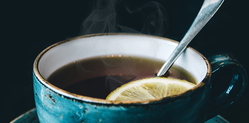 A hot cup of tea with a sliced lemon and spoon in it