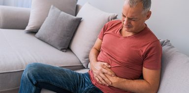 Man sitting on couch holding his stomach in pain