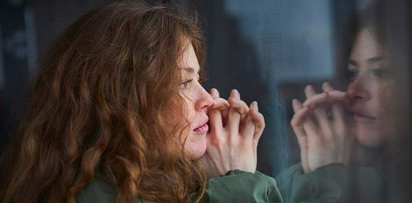 A girl with red hair staring out a window.