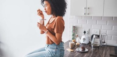 A woman sitting on a kitchen counter eating probiotic yogurt.