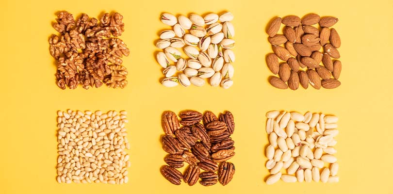 An assortment of nuts against a yellow background.