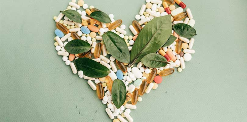 Supplements in the shape of a heart with leaves on top.