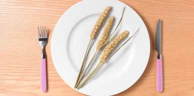 Three strands of wheat on a white plate against a light wood background.